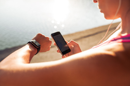 Foto de Sportswoman looking at smartwatch and holding smart phone in her other hand, outdoors. Fitness female setting up her smartwatch for her run. - Imagen libre de derechos