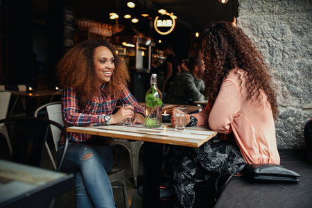 Photo pour Two young women talking sitting in a restaurant. African woman smiling and chatting with her friend in a cafe. - image libre de droit