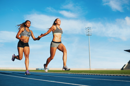 Photo pour Young woman running a relay race and giving relay baton to her teammate. Female runner passing the relay baton during race. - image libre de droit