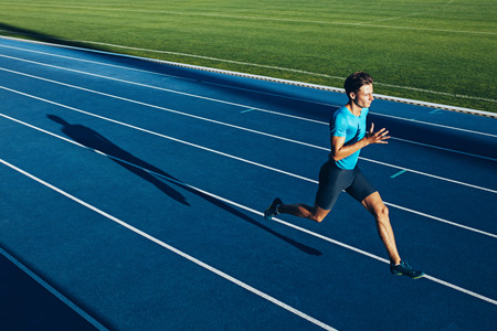 Photo pour Shot of a young male athlete training on a race track. Sprinter running on athletics tracks. - image libre de droit