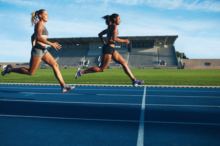 Photo pour Athletes arrives at finish line on racetrack during training session. Young females competing in a track event. Running race practicing in athletics stadium. - image libre de droit