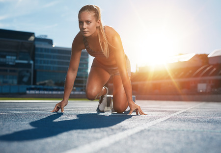 Foto de Fit and confident woman in starting position ready for running. Female athlete about to start a sprint looking away. Bright sunlight from behind. - Imagen libre de derechos