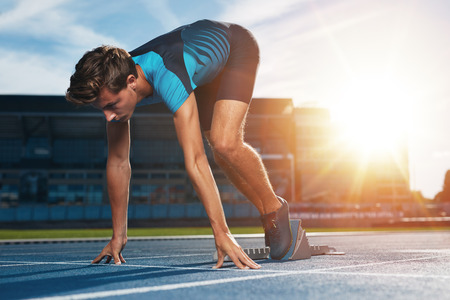 Young male runner taking ready to start position against bright sunlight. Sprinter on starting block of a racetrack in athletics stadium.
