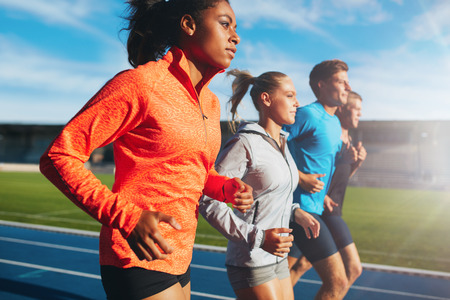Young african woman running with her team on running track in stadium. Multiracial team of runner practicing at athletics stadium on a sunny day.