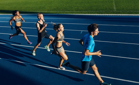 Photo pour Group of multiracial athletes practicing running on racetrack. Male and female athletes during running session at athletics stadium. - image libre de droit
