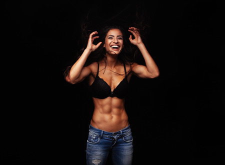 Portrait of cheerful young woman in bra and jeans. Muscular female model laughing on black background.