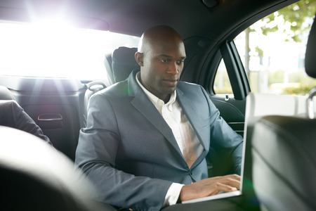 Shot of happy young businessman traveling to work in the luxury car on the back seat and using laptop. African business associate working inside the car.