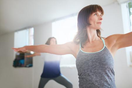 Shot of fitness woman doing yoga. Women exercising at yoga class. Virabhadrasana pose.