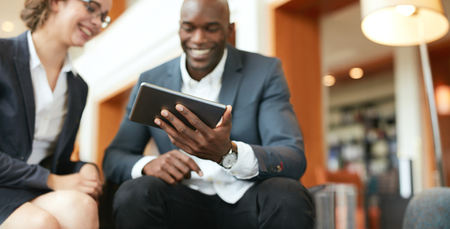 Happy young business people sitting together using digital tablet while at hotel lobby. Focus on tablet computer.