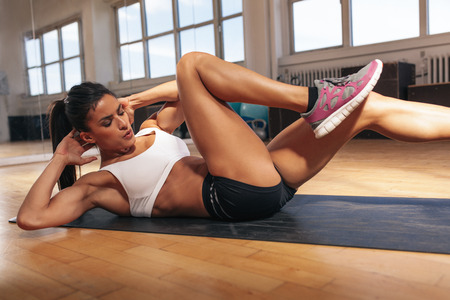 Foto de Young fit woman exercising in a gym lying on mat doing leg raising and twisting exercises. Young attractive woman doing abs workout. Fitness woman doing a sit up. - Imagen libre de derechos