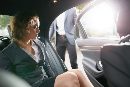 Photo pour Man opening a passenger door for a businesswoman getting out of a car. Female entrepreneur travelling to office in a luxurious car. - image libre de droit