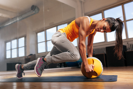 Fit female doing intense core workout in gym. Young muscular woman doing core exercise on fitness mat in health club.