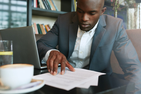 Photo pour Businessman in a coffee shop reading a contract document. African business executive sitting at cafe working. - image libre de droit