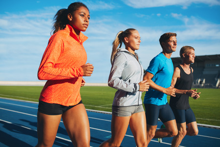 Photo pour Group of diverse sports person practicing running in stadium. Male and female athletes running together on racetrack. - image libre de droit