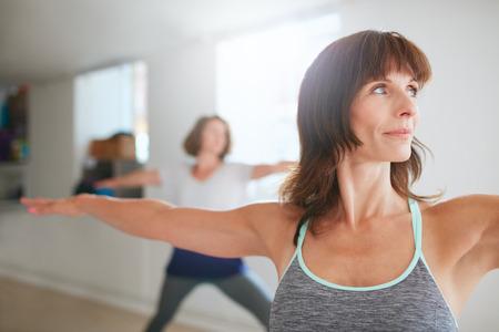 Foto de Portrait of beautiful young woman doing the warrior pose during yoga class. Yoga instructor performing Virabhadrasana position in gym. - Imagen libre de derechos