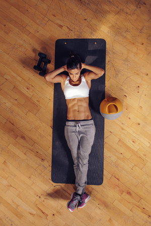 Fit young woman lying on exercise mat doing stomach exercises. Overhead view of female working out at the gym