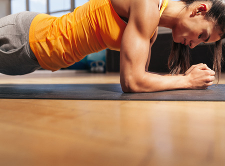 Foto de Cropped shot of woman exercising in the gym. Muscular female doing core workout on fitness mat with copy space. - Imagen libre de derechos