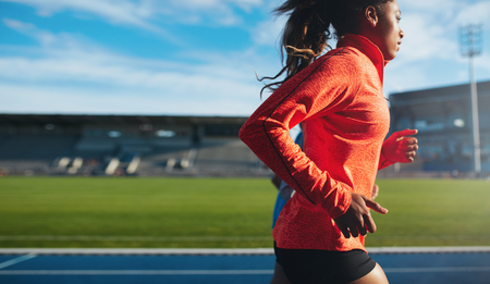 Foto de Side view of fit young woman running. African female athlete training on race track at athletics stadium. - Imagen libre de derechos