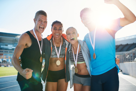 Photo pour Portrait of ecstatic young runners with medals celebrating success in athletics stadium. Young men and women looking excited after winner a running race. - image libre de droit