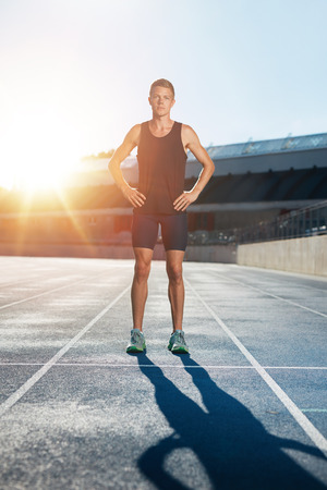 Full length shot of professional male athlete standing with his hands on hips looking confidently at camera. Sprinter on race track in athletics stadium with sun flare.
