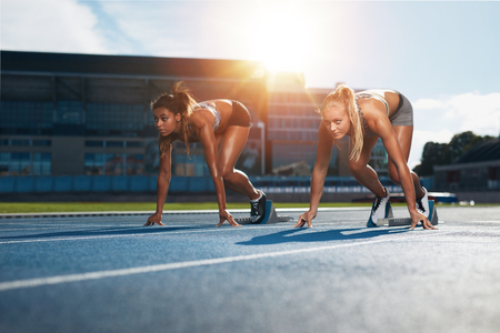 Two female athletes at starting position ready to start a race. Sprinters ready for race on racetrack with sun flare.