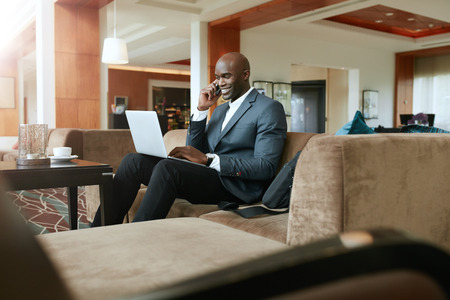 Photo for Happy young businessman sitting on sofa working using cell phone and laptop. African male executive waiting in hotel lobby. - Royalty Free Image