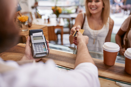 Customer paying for their order with a credit card in a cafe. Bartender holding a credit card reader machine and returning the debit card to female customer after payments.