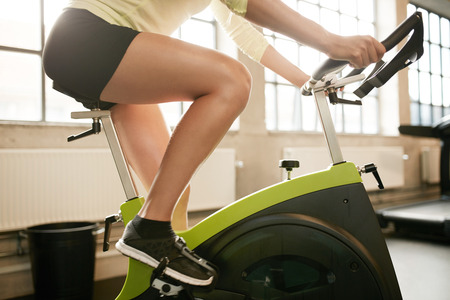 Foto de Cropped shot of fitness woman working out on exercise bike at the gym. Female exercising on bicycle in health club, focus on legs. - Imagen libre de derechos