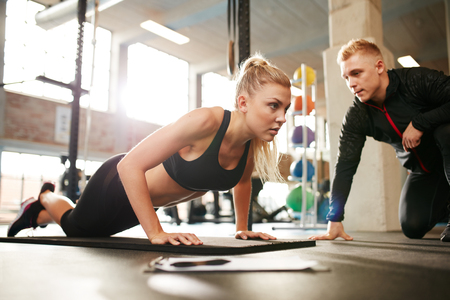 Fitness woman exercising with fitness trainer in gym. Woman doing push ups exercise with her personal trainer at health club.