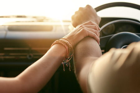Photo pour Close up shot of loving couple traveling by car and holding hands. Focus on hands of man and woman in a road trip. - image libre de droit