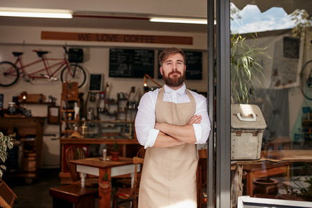 Photo for Shot of cafe owner standing proudly in the doorway of his restaurant. Young man wearing an apron standing with his arms crossed at the door of a cafe. - Royalty Free Image