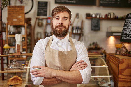Portrait of young man wearing apron standing with his arms crossed in a coffee shop. Caucasian man with beard standing in a cafe looking at camera.