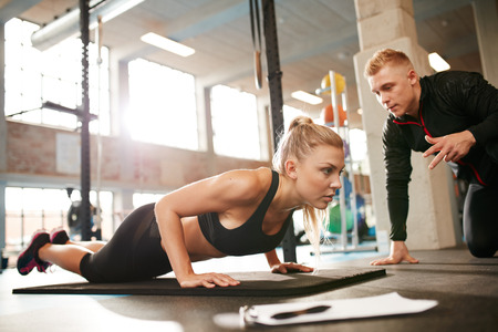 Photo pour Indoor shot of young female exercising with personal trainer at gym. Fitness woman doing push ups with her personal trainer at health club. - image libre de droit
