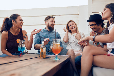 Photo for Portrait of happy young people sitting together and laughing. Multiracial friends enjoying at a party with cocktails on table. - Royalty Free Image