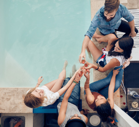 Top view of group of friends toasting at party by a swimming pool. High angle shot of young people sitting by the pool having wine. Men and women partying by the pool.