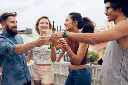 Friends enjoying cocktails at a party. Friends having fun and drinking cocktails outdoor on a rooftop get together. Group of friends toasting drinks outdoors.