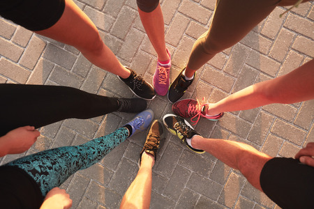 Photo pour Legs of athletes wearing sports shoes in a circle. Top view of runners standing together. - image libre de droit
