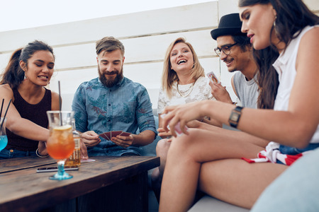 Foto de Group of friends sitting at a wooden table and playing cards. Cheerful young people partying together and playing cards. - Imagen libre de derechos