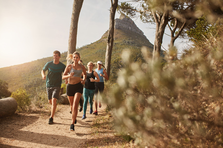 Foto de Group of young adults training and running together through trails on the hillside outdoors in nature. Fit young people trail running on a mountain path. - Imagen libre de derechos