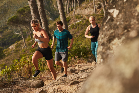 Photo pour Group of runners running on rocks up a hill. Young people running cross country. - image libre de droit