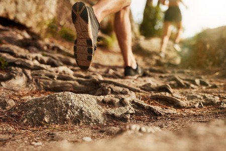 Photo pour Cross country running. Closeup of male feet run through rocky terrain. Focus on shoes. - image libre de droit
