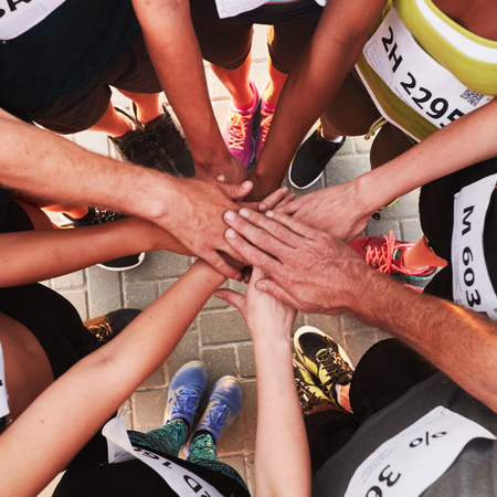 Foto de Hands of running team stacked on top of each other. Top view of a sports team standing in a circle with their hands stacked. - Imagen libre de derechos