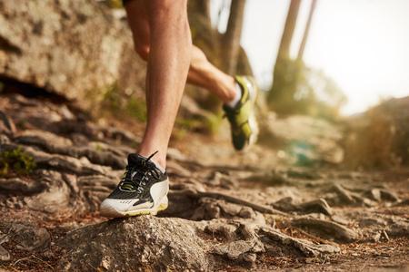 Foto de Close-up of trail running shoe on challenging rocky terrain. Male runner's legs working out on extreme terrain outdoors. - Imagen libre de derechos