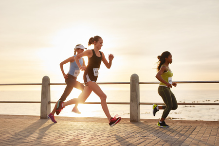 Photo pour Three young women running on a road by the sea. Group of divers runners training on seaside promenade during sunset. - image libre de droit