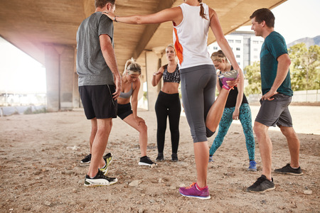 Photo pour Group of young friends stretching under a bridge after a morning run. Running club group taking a break from training. - image libre de droit
