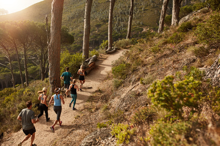 Foto de Group of young people trail running on a mountain path. Runners working out in beautiful nature. - Imagen libre de derechos