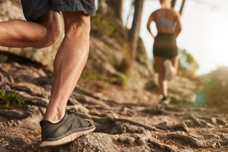 Photo pour Closeup of male feet run through rocky terrain. Cross country running with focus on runner's legs. - image libre de droit