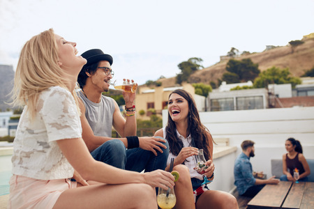 Foto de Happy young people having drinks and enjoying while their friends sitting and talking to each other in the background. Young men and women having rooftop party. - Imagen libre de derechos
