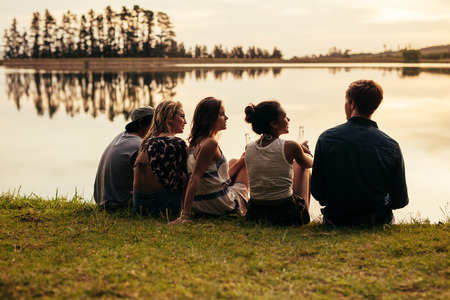 Rear view portrait of group of young friends relaxing by a lake. Young people sitting together by a lake.