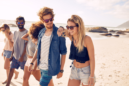 Foto per Diverse group of young friends having a walk on the beach. Young people looking happy on vacation. Young men and woman walking on coast. - Immagine Royalty Free